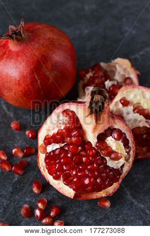 Juicy fresh pomegranates on black marble background
