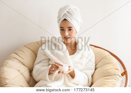 Beautiful young woman with jar of cream in spa salon