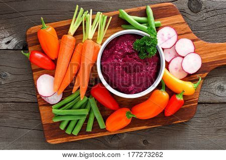 Beet Hummus Dip With A Serving Platter Of Fresh Vegetables, Above View On A Wood Background