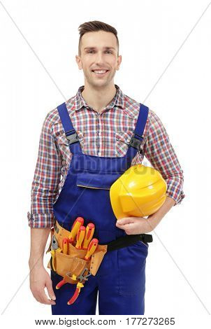 Young electrician with tools and helmet on white background