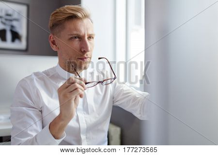 Horizontal indoors shot of thoughtful man holding his glasses and looking at the PC screen.