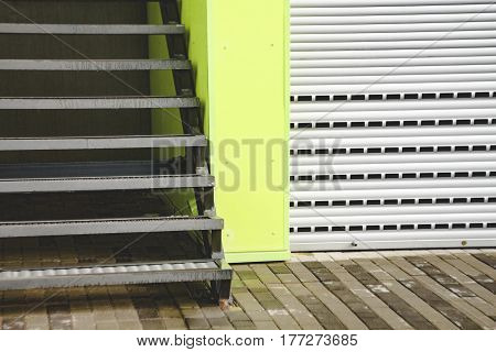 Steps in a modern building and a roller shutter door. background