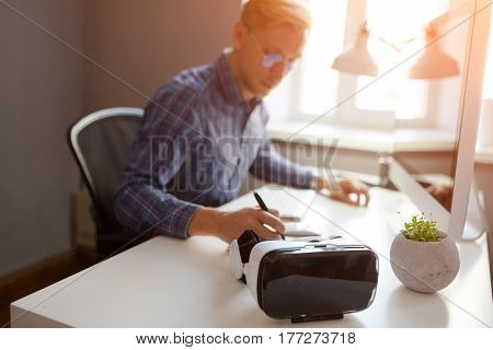 The VR goggles placed near the man writing sitting at the desktop.