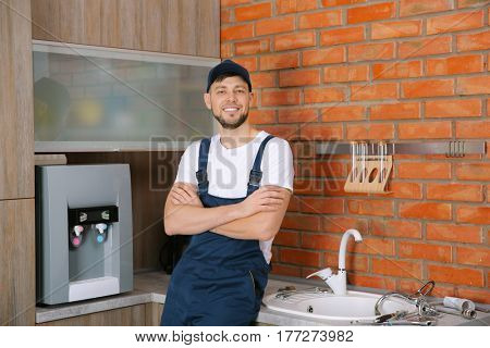 Plumber with crossed arms standing at kitchen