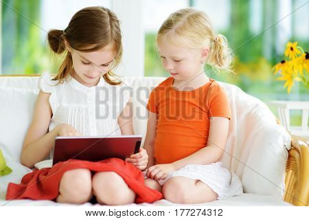 Two Adorable Little Sisters Playing With A Digital Tablet
