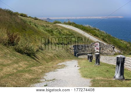 Photo of a park with green grass, sea and sunlight