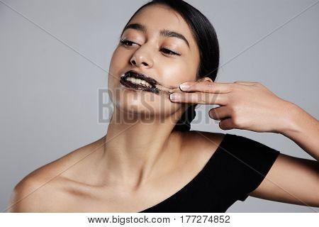 mixed race woman smudge a lip scrub on cheek