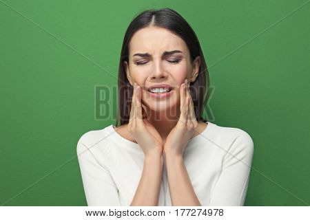 Beautiful young woman suffering from toothache on color background