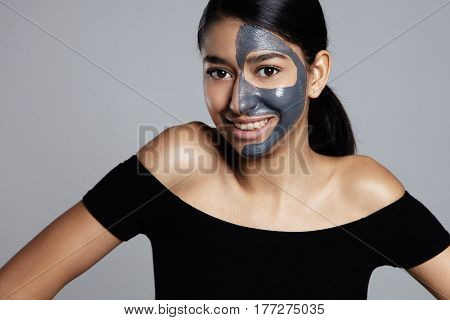 mixed race woman smiling with a half of face in mask