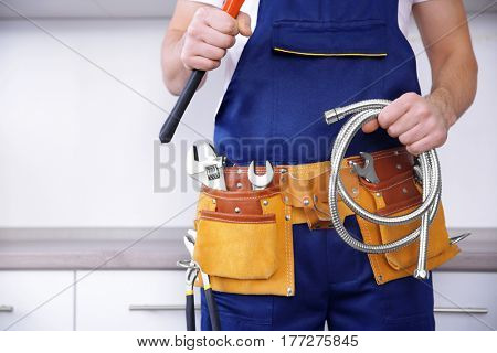 Plumber in uniform holding pipe wrench at kitchen