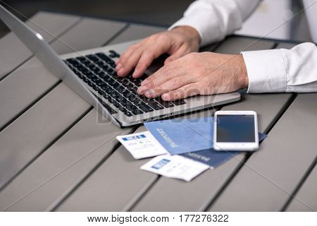 Young man using laptop booking tickets tour agency