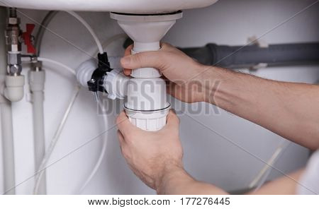 Plumber repairing sink pipes in kitchen, closeup