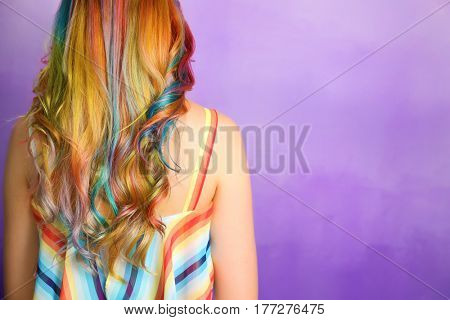 Trendy hairstyle concept. Young woman with colorful dyed hair on color background