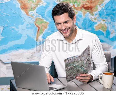 Young man tour agent sitting in office browsing laptop