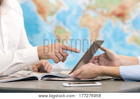 Young man and woman sitting in office travel agency