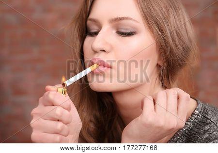 Young woman lighting cigarette, closeup