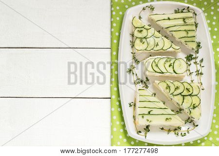 Delicious spring sandwiches with cream cheese fresh cucumbers and thyme leaves on a plate on a white wooden background