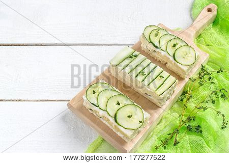 Delicious spring sandwiches with cream cheese fresh cucumbers and thyme leaves on a wooden board on a white background