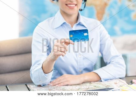 Young woman sitting in office travel agency holding credit card