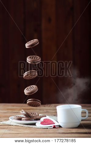 Cookies In Flight And A Cup Of Hot Tea, Close-up On A Wooden Table.