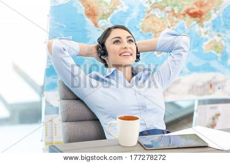Young woman sitting in office travel agency relaxed