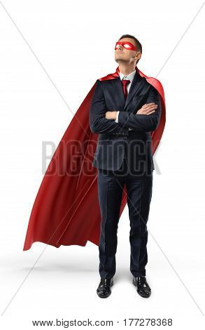 A businessman in an official suit and red cape with hands crossed and looking up. Business development. Success and planning. Future projects.