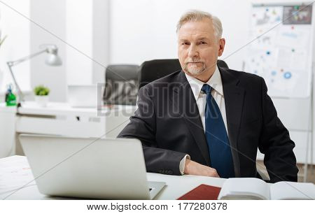 Full of determination. Concentrated confident bearded businessman sitting in the office while working and expressing confidence