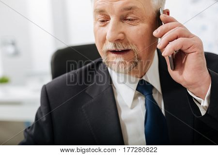 Interesting working hours. Smiling charming aged employer sitting in the office while expressing interest and using phone