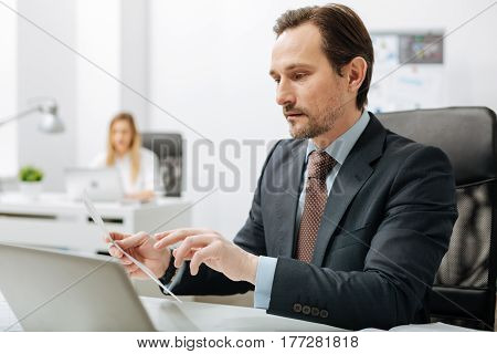 Checking the statistics of the company. Involved experienced persistent executive sitting in the office and reading documents while his subordinate working in the background