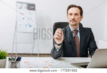Choosing the next member of our team. Concentrated experienced bearded recruiter sitting in the office and pointing out at the audience while expressing confidence