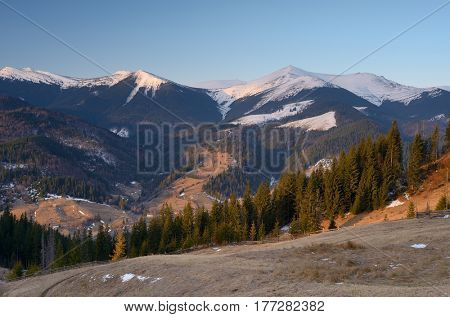 Spring landscape with a view of the mountain village. The last snow on the peaks. Carpathians, Ukraine, Europe
