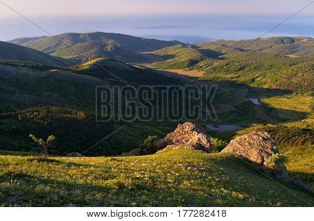 Summer landscape overlooking the sea. Green hills with forest. Sunny morning