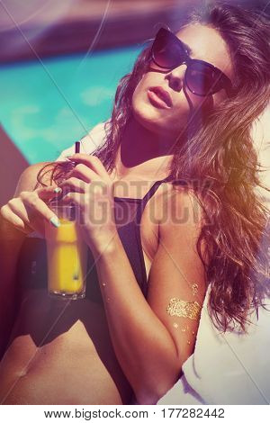 attractive girl in bikini and sunglasses enjoy in sun and juice at pool hot summer day