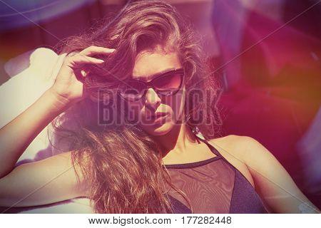 attractive  girl in bikini and sunglasses enjoy in sun summer day at pool
