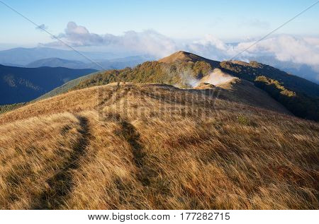 Autumn landscape with dry grass. Road in the mountains. Sunny evening with low clouds. Borzhava Range, Carpathians, Ukraine, Europe