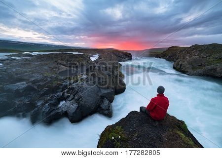 Tourist attraction in the north of Iceland. Ahead of the waterfall Godafoss. Skjalfandafljot river near the town of Akureyri. Tourist sits on a rock and looks at the midnight sun