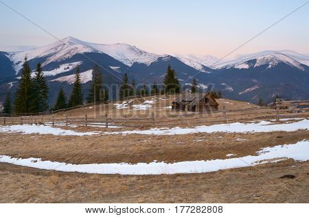 Spring landscape with old wooden barn. Village in the mountains with a view of the snowy peaks. Predawn twilight. Carpathians, Ukraine, Europe