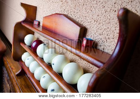 Horizontal photo of Set of balls for a game of pool billiards on shelves. Russian pool billiard. Pool billiard game. Billiard sport concept art.