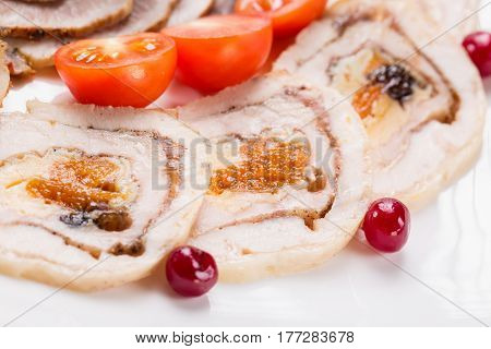 Meat rolls with cherry tomatoes and cranberry on white plate. Close up with selective focus.