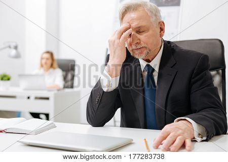 Full of desperation. Bearded upset despaired businessman sitting in the office and touching his head while expressing emotions