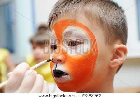 Make up artist making tiger mask for child.Children face painting. Boy painted as tiger or ferocious lion. Preparing for theatrical performance. Boy actor playing role. Tiger mask face poster