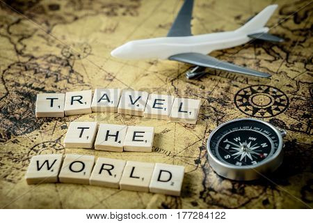 Travel the world concept scrabble text and traveler equipment on vintage map