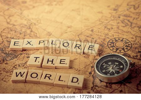 Explore the world concept scrabble text and traveler equipment on vintage map