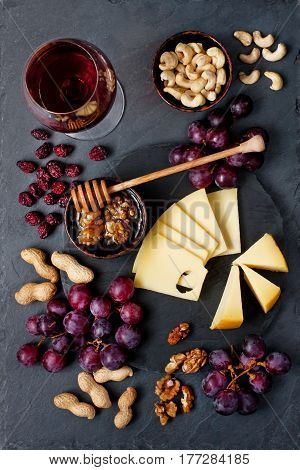Composition with grape, cheese, wine glass  and honey