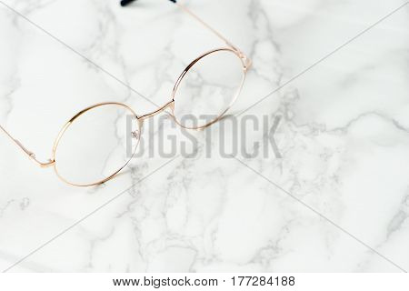 Golden metal Eyeglasses on luxury marble surface