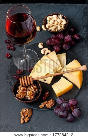 Wine, cheese, grapes, honey on stone background