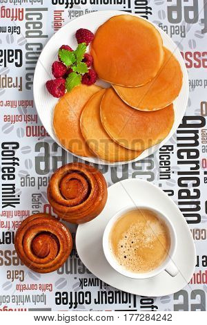Breakfast composition with coffee cup, pancakes and sweet buns