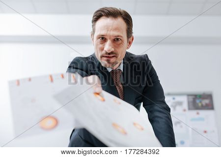 Full of negative emotions. Furious irritable aged businessman standing in the office and throwing documents about while expressing fierce