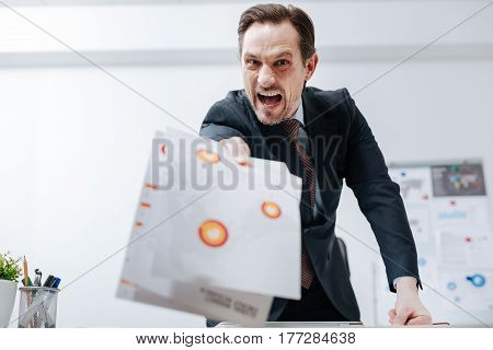 Firing you. Fierce irritable angry boss standing in the office and holding documents while expressing fierce and dismissing the employee