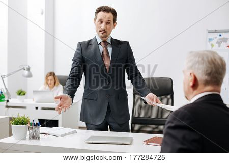 Little misunderstanding between us . Surprised confused pleasant employer standing in the office while working and having conversation with colleague